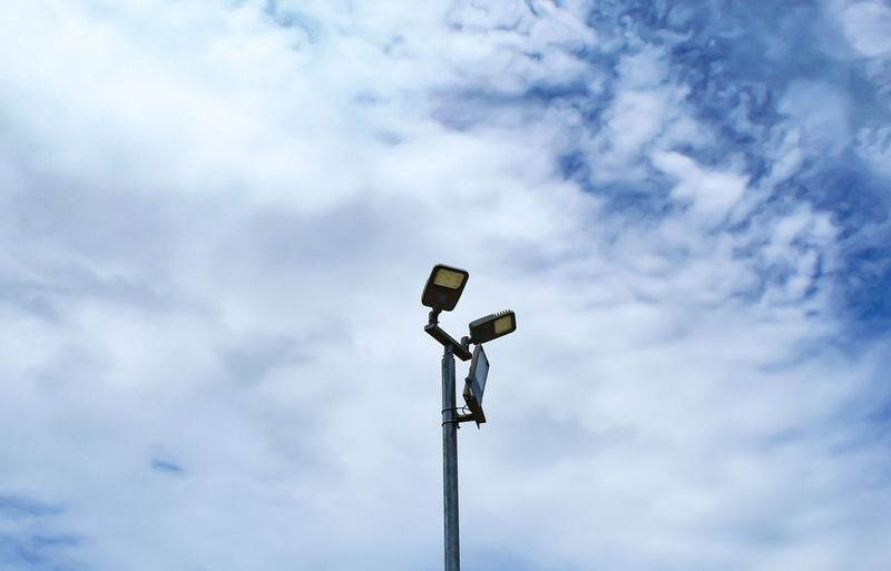 Low angle view of electrical equipment against sky