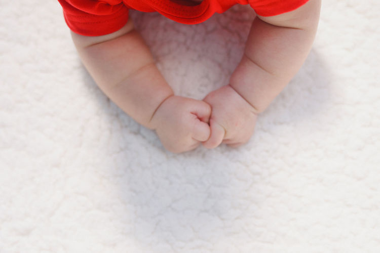 High angle view of baby arms on carpet