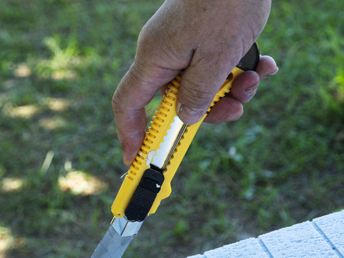 Close-up of hand holding yellow utility knife