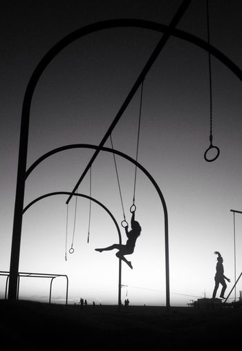 Silhouette Of Persons Swinging On Gym Rings