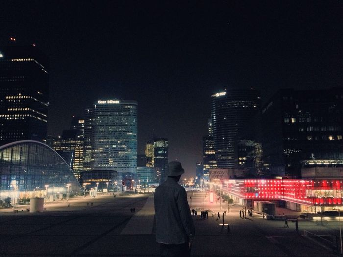 Rear view of woman standing in city at night