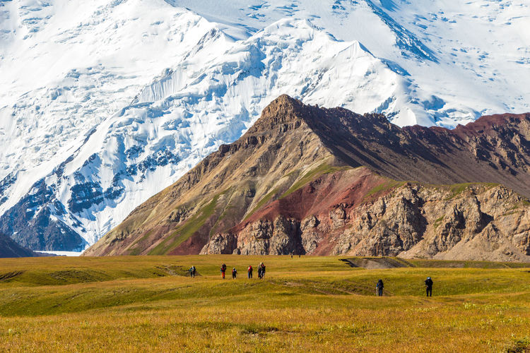 People walking on field against mountains during winter