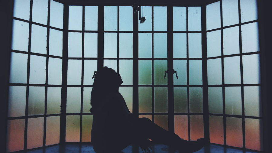Silhouette Woman Sitting By Glass Window