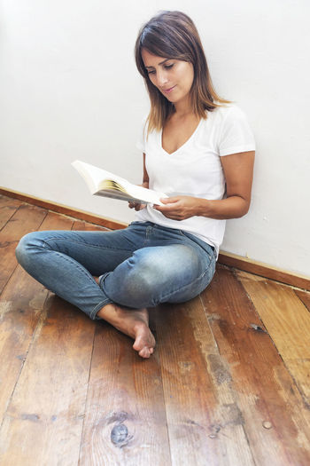 side view of a beautiful woman sitting on ground leaning on a white wall while reading a book Casual Clothing Full Length Young Adult Young Women One Person Indoors  Sitting Flooring Lifestyles Wood Home Interior Real People Front View Holding Hardwood Floor Leisure Activity Women Cross-legged Activity Hairstyle Beautiful Woman Jeans Reading Reading A Book Book Literature Jeans T-shirt Flooring