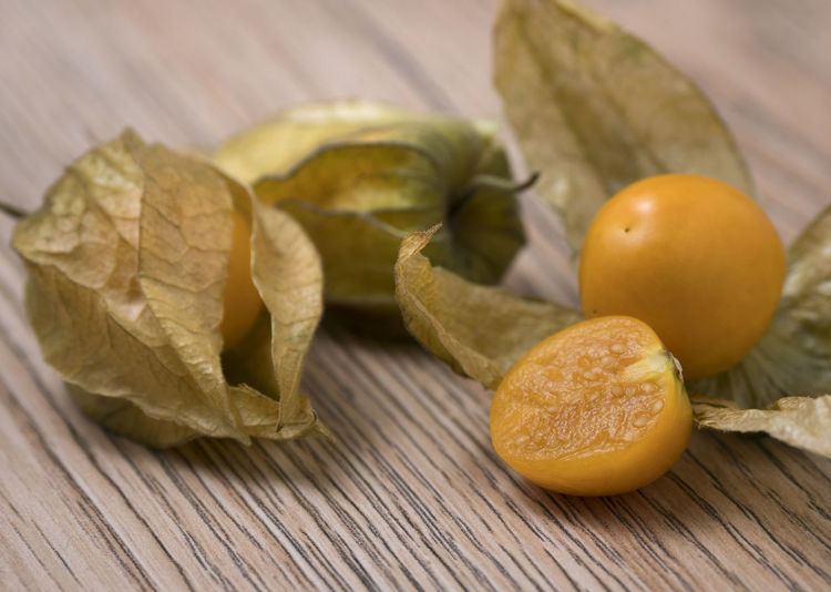 Physalis fruit (Physalis Peruviana) with husk on wooden background. Close up view. Physalis; Orange; Fruit; Isolated; Berry; Food; Cherry; Sweet; Fresh; Lantern; White; Tasty; Ripe; Nature; Small; Exotic; Healthy; Husktomato; Husk; Tomato; Diet; Plant; Golden; Culinary; Juicy; Gooseberry; Background; Round; Ground; Season; Yellow; Heap; Food And Drink Food Healthy Eating Table Wellbeing Wood - Material Freshness Close-up Fruit Still Life Indoors  No People Leaf Focus On Foreground Plant Part Group Of Objects Yellow SLICE Orange Color Citrus Fruit Leaves