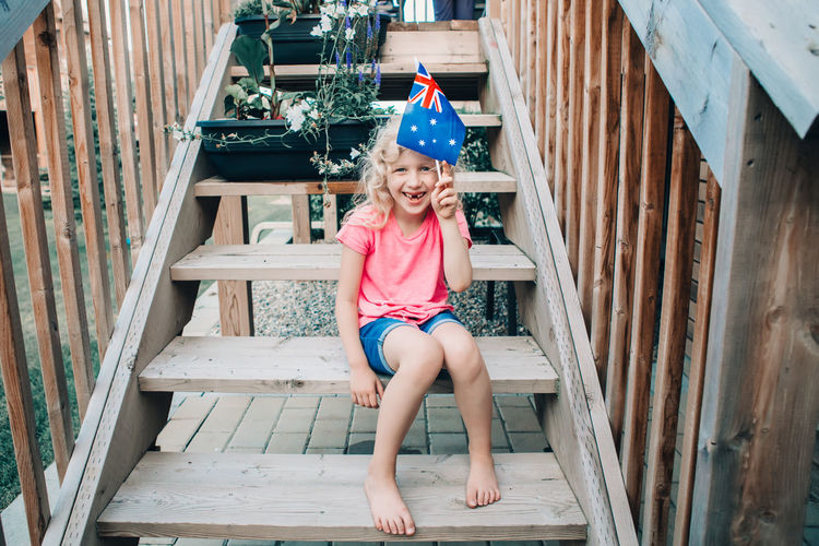 Adorable cute happy caucasian girl holding australian flag. kid celebrating australia day holiday