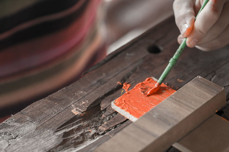 Close-Up Of Men Painting Wood