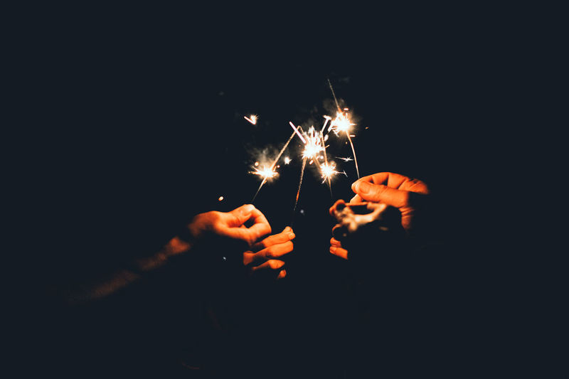 Close-up of friends holding illuminated sparklers at night