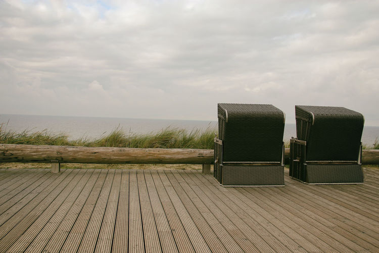 Hooded Beach Chairs On Wooden Boardwalk By Sea Against Cloudy Sky
