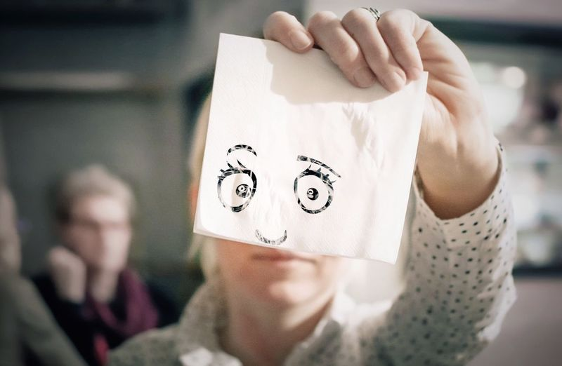 Optical illusion of woman holding anthropomorphic face on tissue