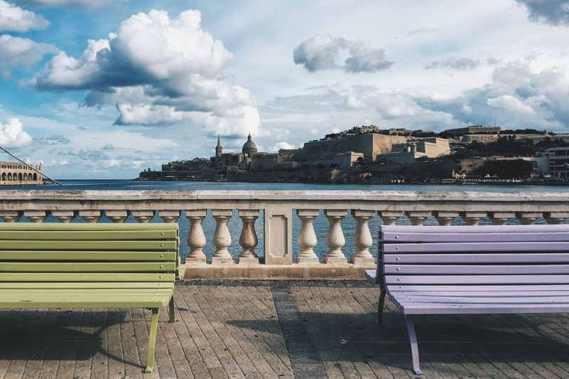 Empty benches on bridge against cloudy sky