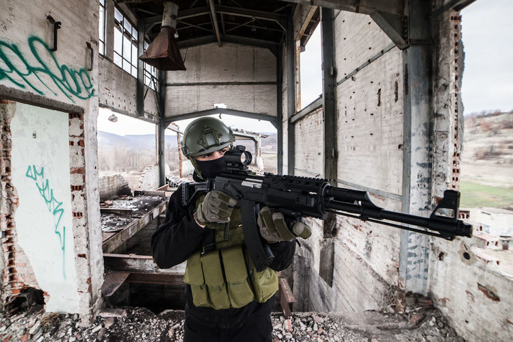 Gun Weapon One Person Aiming Security Military Protection Helmet Safety Government Armed Forces Uniform Standing Day Military Uniform Rifle Clothing Headwear Camouflage Clothing Machine Gun Special Forces Obscured Face