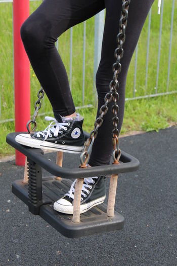 Black Color Black. Casual Clothing Child On A Swing. Childs Swing. Close-up Day Footwear Legs.  Lifestyles Low Section Outdoors Park Part Of Person Red Sneakers. Fashion. Swing...