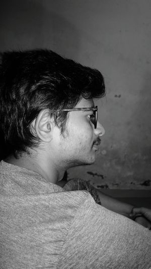 Profile view of thoughtful young man wearing eyeglasses against wall