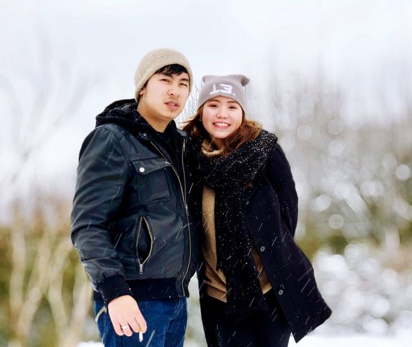 Portrait of friends wearing warm clothing during snowfall