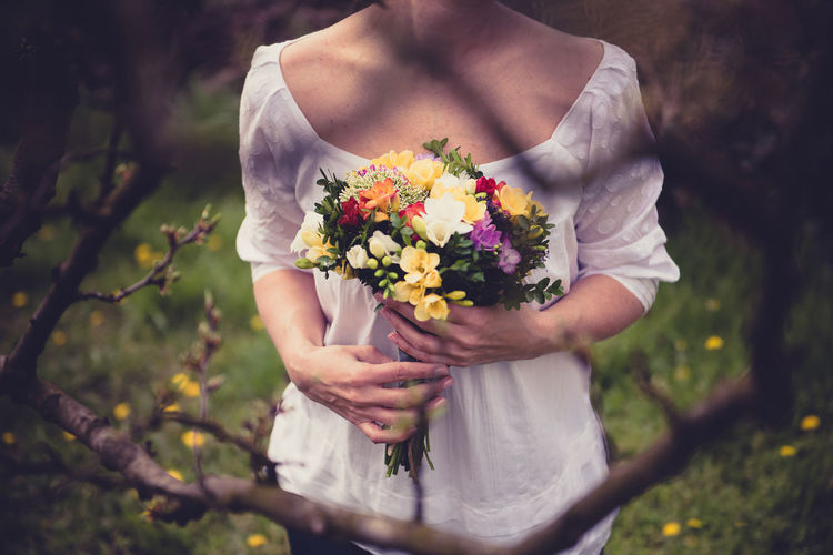 Bouquet Flower Field Standing Person Fragility Vignette Freshness Female Beauty In Nature In Front Of Holding Midsection Bouquet Dress Nature White Color One Person Outdoors Young Adult Human Hand Flower Head Adult