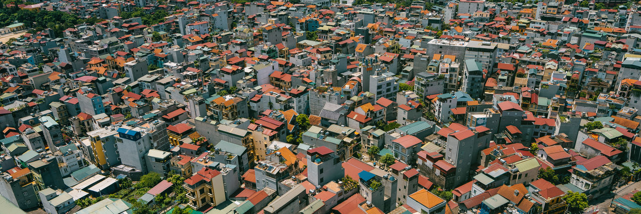 High angle view of tree and houses in city