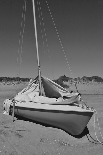 Sailboats moored on beach against clear sky
