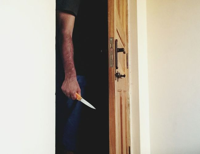 Midsection Of Man With Knife Standing Behind Door