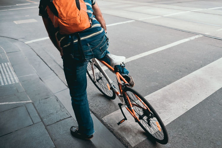 Low section of man with bicycle on road