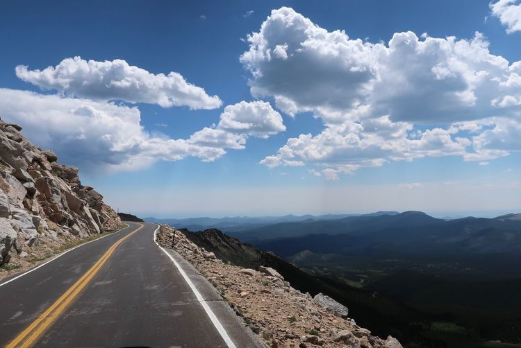 Landscape of road at 14,000 feet on the side of Mount Evans in Colorado Colorado Mount Evans Scenic Byway High Elevation Valley Landscape Sky Cloud - Sky Transportation Beauty In Nature Mountain Direction Road Nature Tranquility Tranquil Scene Mountain Range Non-urban Scene Diminishing Perspective Symbol Scenics - Nature The Way Forward Sign No People Road Marking Cloudscape vanishing point