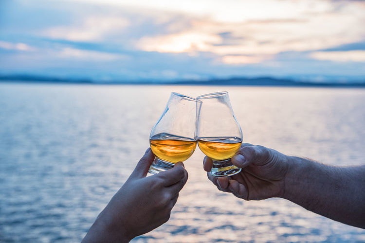 Alcohol B Beautiful Cheers Drinking Focus On Foreground Food And Drink Glasses Holding Lifestyles Outdoors Person Personal Perspective Scotland Sea Sky Stem Sunset Toast Traveling Unrecognizable Person Vacation Whiskey