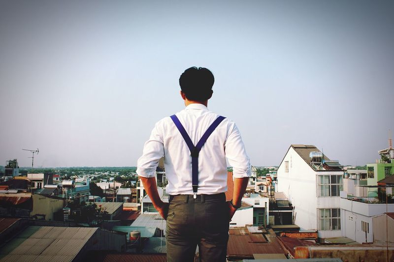 Rear view of man looking at cityscape against clear sky