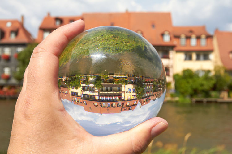 Cropped Hand Holding Crystal Ball With Reflection Of Houses