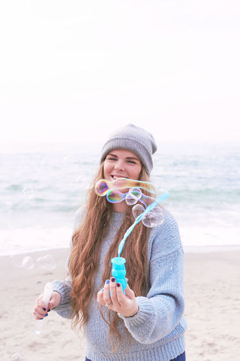 Happy young woman with long hair having fun with bubbles in autumn at the beach person