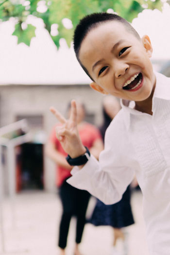 Portrait of cheerful boy gesturing peace sign outdoors