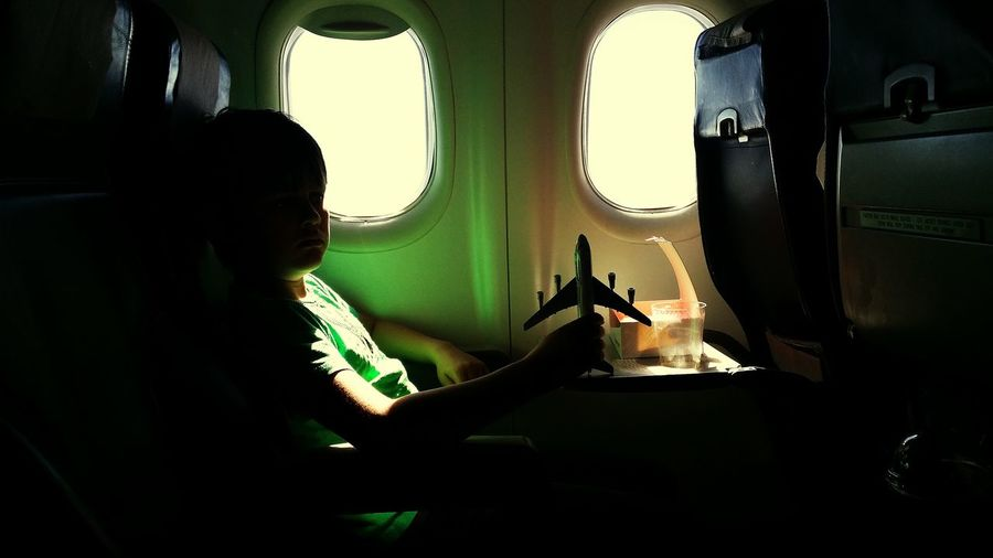Boy Holding Toy While Sitting In Airplane