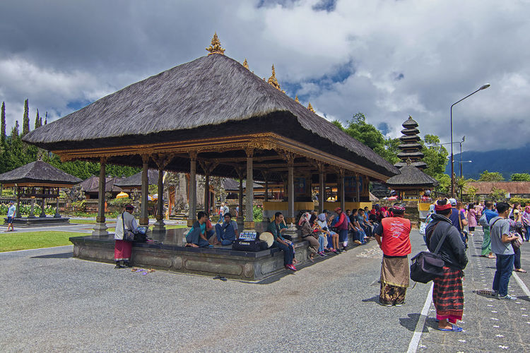 Group of people outside temple against sky
