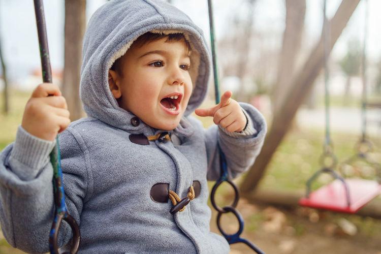 Cute boy enjoying on swing at playground