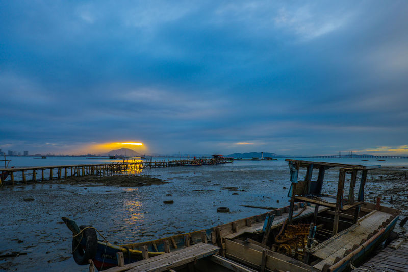 Old abandoned wooden boat at beach against cloudy sky at dusk