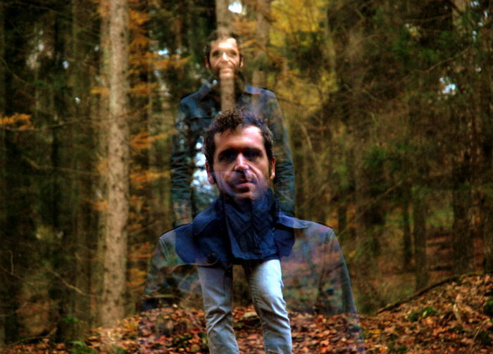 Multiple Image Of Mid Adult Man Standing Against Trees In Forest
