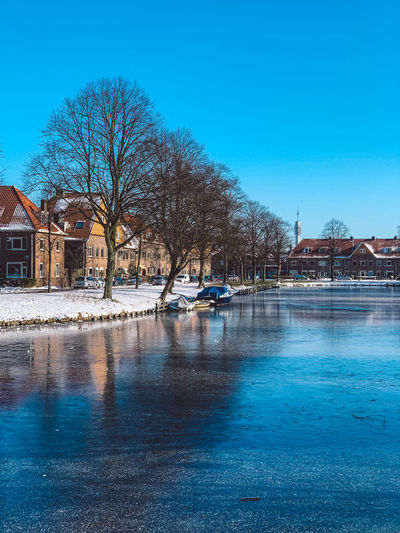Scenic view of frozen canal by buildings against clear blue sky