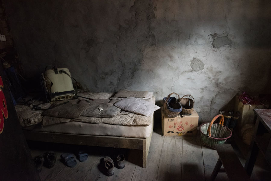 In the Qin minority village of Western Sichuan, China, the beekeper sleeps in a dimly lit room with bare floor and walls, sharing the bed with grimy mats and baskets. Bare Living Poor  Rural Sichuan Basic Bed Bedroom China Chinese Dirty Domestic Room Grey Grime Grimy Home Home Interior Indoors  Life In China Old Poverty Simple