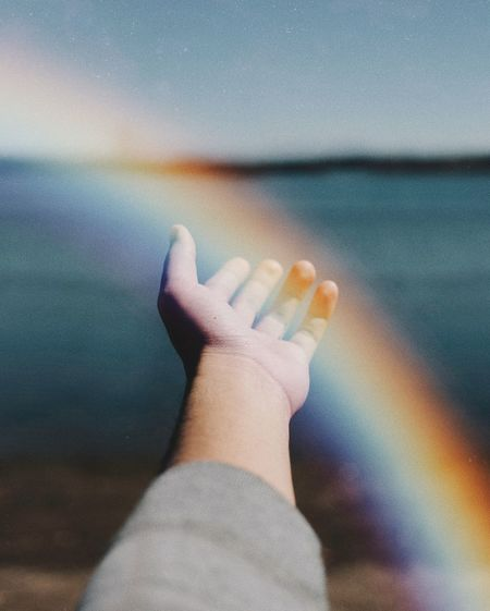 Close-up of hand against sea and sky