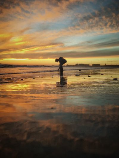 Man standing on beach against cloudy sky during sunset