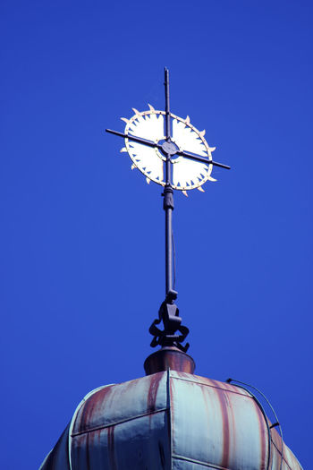 Low angle view of weather vane against clear blue sky
