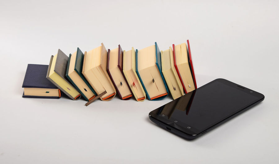 Evolution of information, media and entertainment, smatrphone and small pocket books Books Close-up Education Entertainment Evolution  Fun Hobbies Improvement Information Information Medium Knowledge Leisure Leisure Activity Library Media New No People Old Overload Phone Progress Reading Smartphone Technology Time