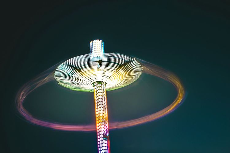 Low angle view of illuminated chain swing ride against clear sky at night
