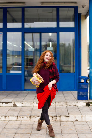 A cheerful red-haired young woman comes out of the store with bread