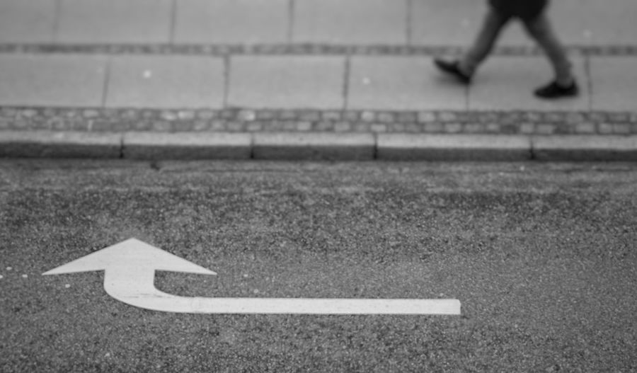 Low section of person with arrow sign on road