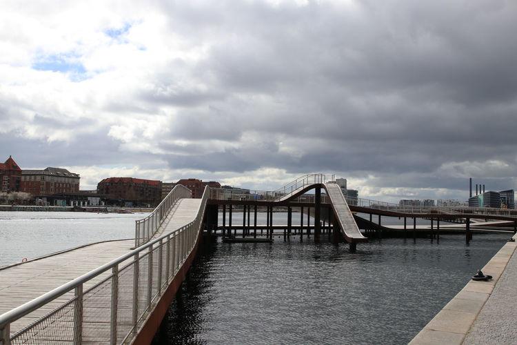 Bridge over water in city against sky