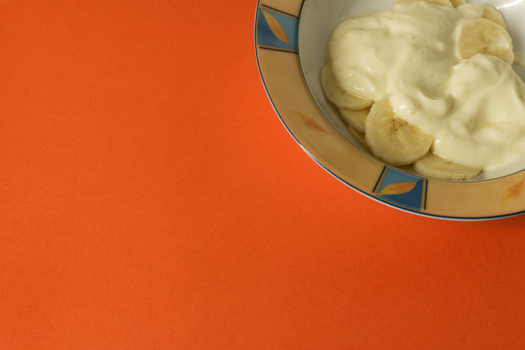 Bowl of sliced banana and yoghurt in a bowl on bright orange background - minimal, copy space EyeEmNewHere Yogurt Yoghurt And Fruit Yoghurt Sweet Snack Sliced Banana Simple Food Simple Beauty Ready-to-eat Minimalism Minimal Fruit Bright Colours Bowl Banana And Yoghurt After School Snack Orange Healthy Snack From Above  Everyday Food Everyday Life Copy Space Banana