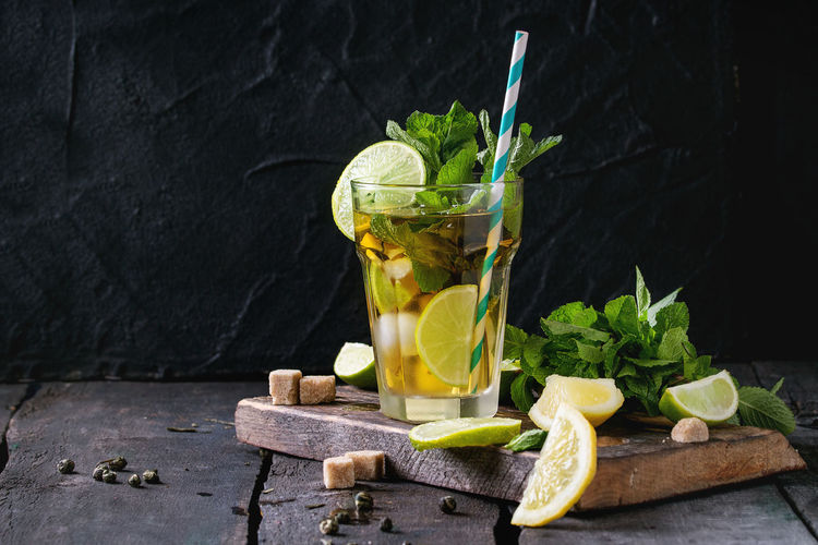 Glass of Iced green tea with lime, lemon, mint and sugar cubes on wooden chopping board over old wooden table. Dark rustic style. Food And Drink Drink Refreshment Food Herb Drinking Glass Mint Leaf - Culinary Glass Leaf Fruit Healthy Eating Freshness No People Cocktail Mojito Lemonade Straw Iced Tea Lime Lemon Sugar Cold Sweet Food Dark Citrus Fruit