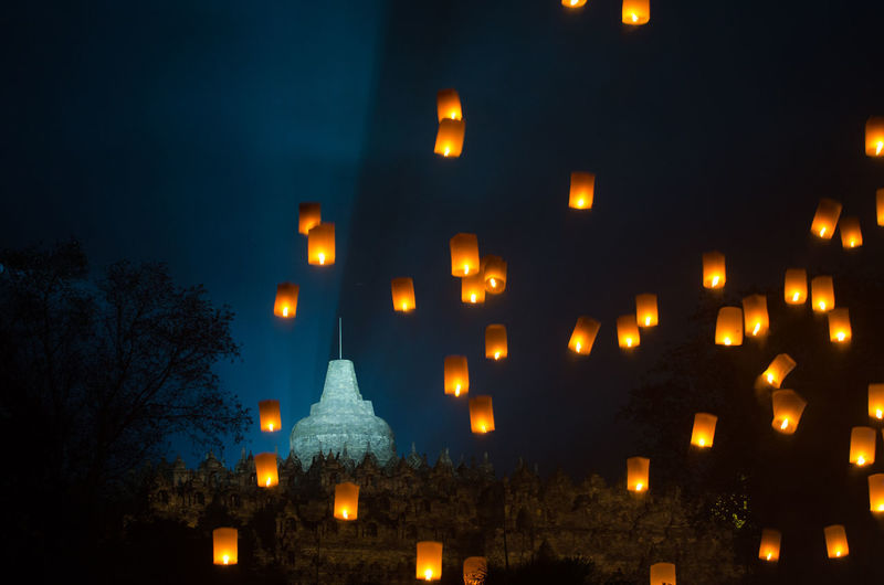 Low angle view of lit paper lanterns moving up at night