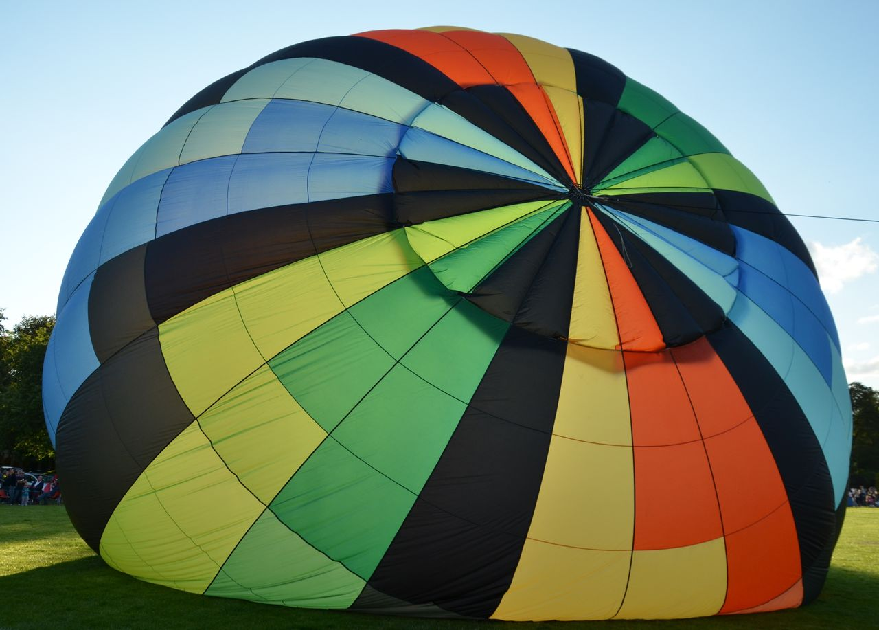 multi colored, hot air balloon, balloon, air vehicle, adventure, transportation, ballooning festival, day, sky, nature, extreme sports, low angle view, no people, parachute, flying, outdoors, mid-air, sport, celebration, inflating, parasailing