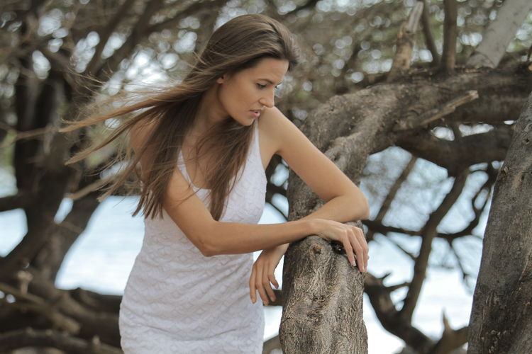 Beautiful mid adult woman wearing dress while standing by tree